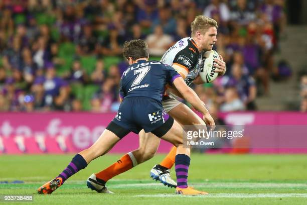 Chris Lawrence of the Tigers is tackled by Brodie Croft of the Storm during the round two NRL match between the Melbourne Storm and the Wests Tigers...