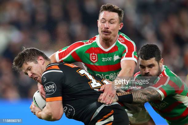 Chris Lawrence of the Tigers is tackled by Damien Cook of the Rabbitohs and Adam Reynolds of the Rabbitohs during the round 15 NRL match between the...
