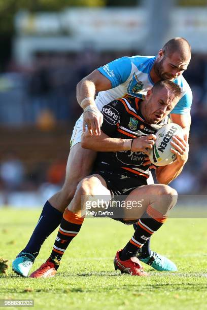 Chris Lawrence of the Tigers is tackled by Tigers defense during the round 16 NRL match between the Wests Tigers and the Gold Coast Titans at...