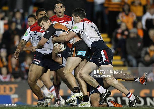 Chris Lawrence of the Tigers is tackled during the round 20 NRL match between the Wests Tigers and the Sydney Roosters at Leichhardt Oval on July 23...