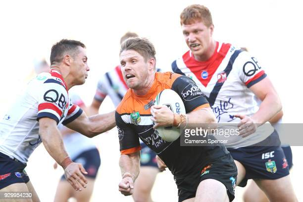 Chris Lawrence of the Tigers is tackled during the round one NRL match between the Wests Tigers and the Sydney Roosters at ANZ Stadium on March 10...