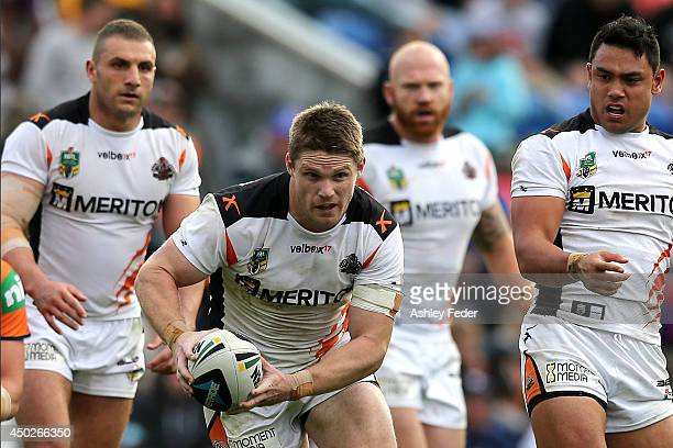 Chris Lawrence of the Tigers runs the ball during the round 13 NRL match between the Newcastle Knights and the Wests Tigers at Hunter Stadium on June...