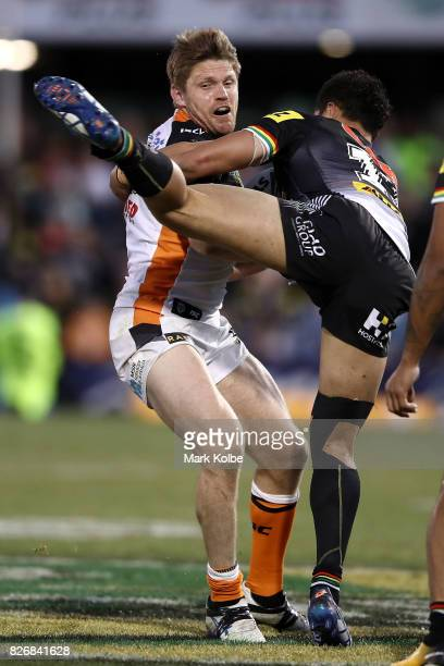Chris Lawrence of the Tigers tackled by Corey HarawiraNaera of the Panthers during the round 22 NRL match between the Penrith Panthers and the Wests...