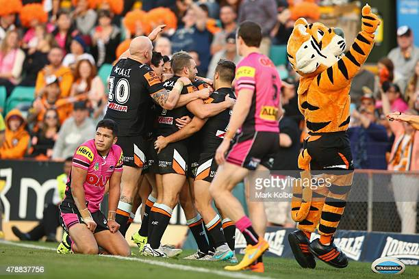 Chris Lawrence of the Wests Tigers celebrates with his team mates after scoring a try during the round 16 NRL match between the Wests Tigers and the...