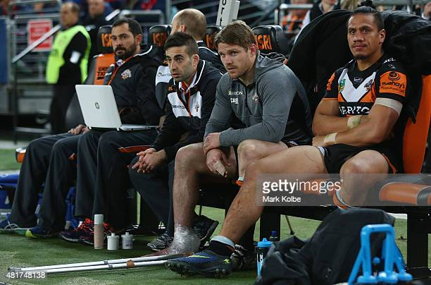 Chris Lawrence of the Wests Tigers watches on from the bench after leaving the field with an injury during the round 20 NRL match between the Wests...