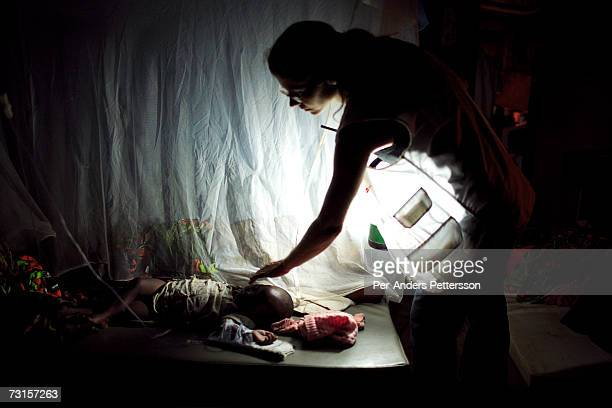 Chris Lenzen, a German medical doctor, checks her patients at night on December 10, 2005 in Dubie, Katanga Province in Congo, Democratic Republic of...