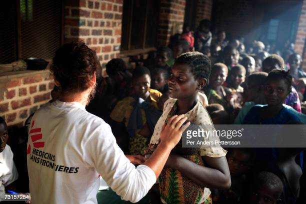 Chris Lenzen, a medical doctor, comforts a baby as she waits with her mother to be vaccinated for measles in a makeshift camp on December 7, 2005 in...