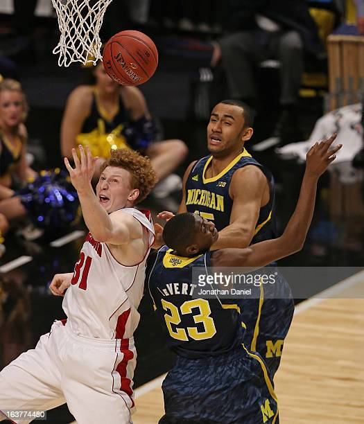 Chris LeVert and Jon Horford of the Michigan Wolverines battle for a rebound with Mike Bruesewitz of the Wisconsin Badgers during a quarterfinal game...