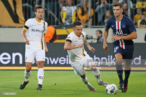 Chris Loewe of Dynamo Dresden Baris Atik of Dynamo Dresden and Thomas Meunier of Paris SaintGermain battle for the ball during the preseason friendly...