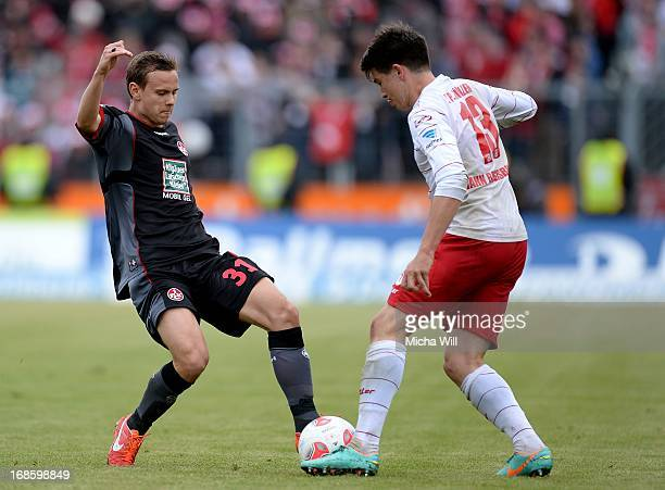 Chris Loewe of Kaiserslautern is challenged by JimPatrick Mueller of Regensburg during the second Bundesliga match at Jahnstadion on May 12 2013 in...