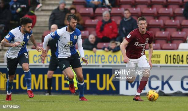 Chris Long of Northampton Town moves forward with the ball away from Derrick Williams and Elliott Ward of Blackburn Rovers during the Sky Bet League...