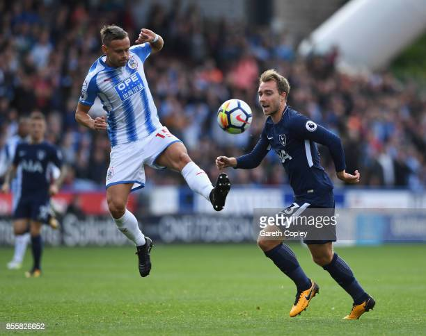 Chris Lowe of Huddersfield Town and Christian Eriksen of Tottenham Hotspur battle for possession during the Premier League match between Huddersfield...
