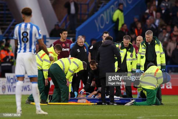 Chris Lowe of Huddersfield Town receives medical treatment during the Premier League match between Huddersfield Town and West Ham United at the John...
