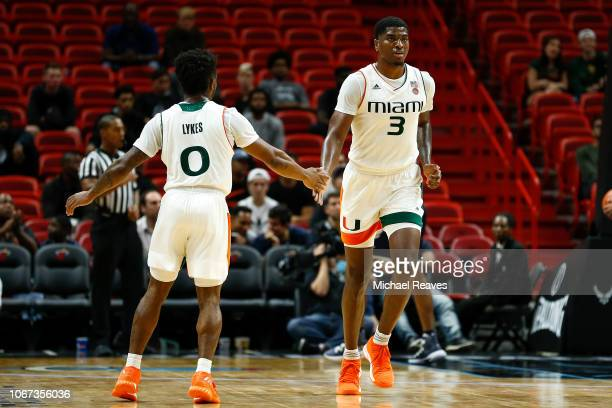 Chris Lykes and Anthony Lawrence II of the Miami Hurricanes celebrate against the Yale Bulldogs during the HoopHall Miami Invitational at American...