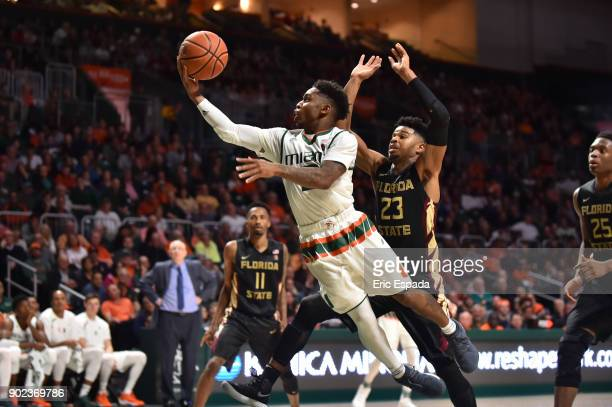 Chris Lykes of the Miami Hurricanes drives to the basket while being defended by MJ Walker of the Florida State Seminoles during the second half of...