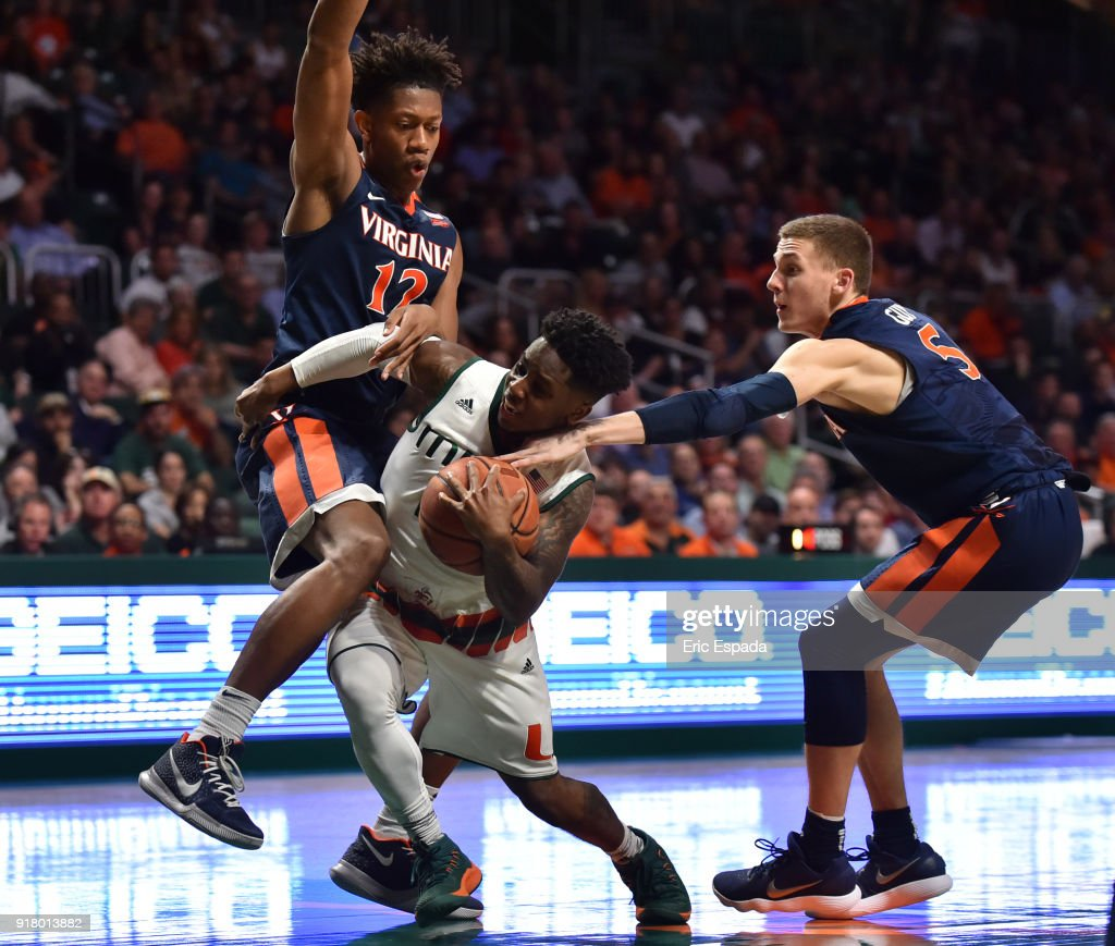 Chris Lykes #2 of the Miami Hurricanes drives to the basket while being defended by De'Andre Hunter #12 and Kyle Guy #5 of the Virginia Cavaliers during the second half of the game at The Watsco Center on February 13, 2018 in Miami, Florida.