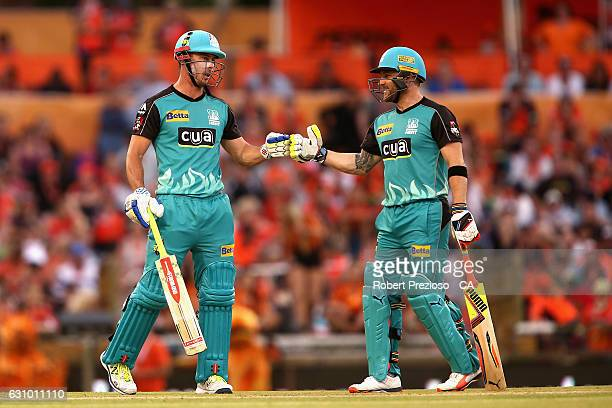 Chris Lynn of the Heat and Brendon McCullum of the Heat touch gloves during the Big Bash League match between the Perth Scorchers and the Brisbane...