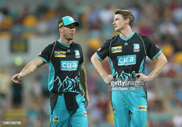 Chris Lynn of the Heat talks to bowler Brendan Doggett during the Big Bash League match between the Brisbane Heat and the Melbourne Renegades at The...