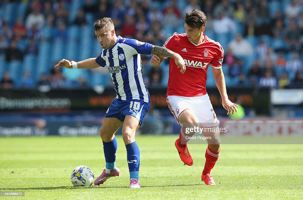 Chris Maguire of Sheffield Wednesday is challenged by Eric Lichaj (R) during the Sky Bet Championship match between Sheffield Wednesday and Nottingham Forest at Hillsborough Stadium on August 30, 2014 in Sheffield, England.