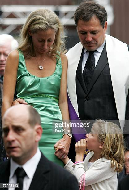 Chris Mainwaring's wife Rani Mainwaring is comforted by Neale Fong as she stands with daughter Maddy Wainwaring as the casket of former West Coast...