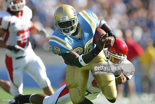 Chris Markey of the UCLA Bruins carries the ball under pressure from Eric Shyne of the Utah Utes during the college football game held on Septemeber...