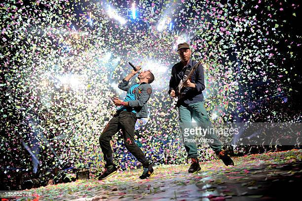 Chris Martin and Jonny Buckland of Coldplay perform onstage at the LanxessArena on December 15 2011 in Cologne Germany