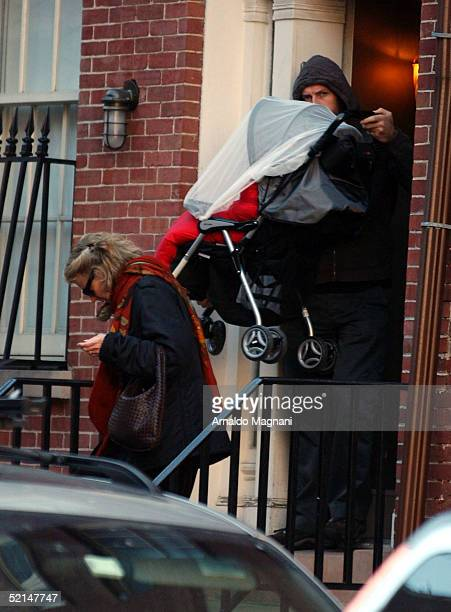 Chris Martin husband of Gweneth Paltrow carries baby Apple in a carriage down the steps with grandmother Blythe Danner February 6 2005 in New York...