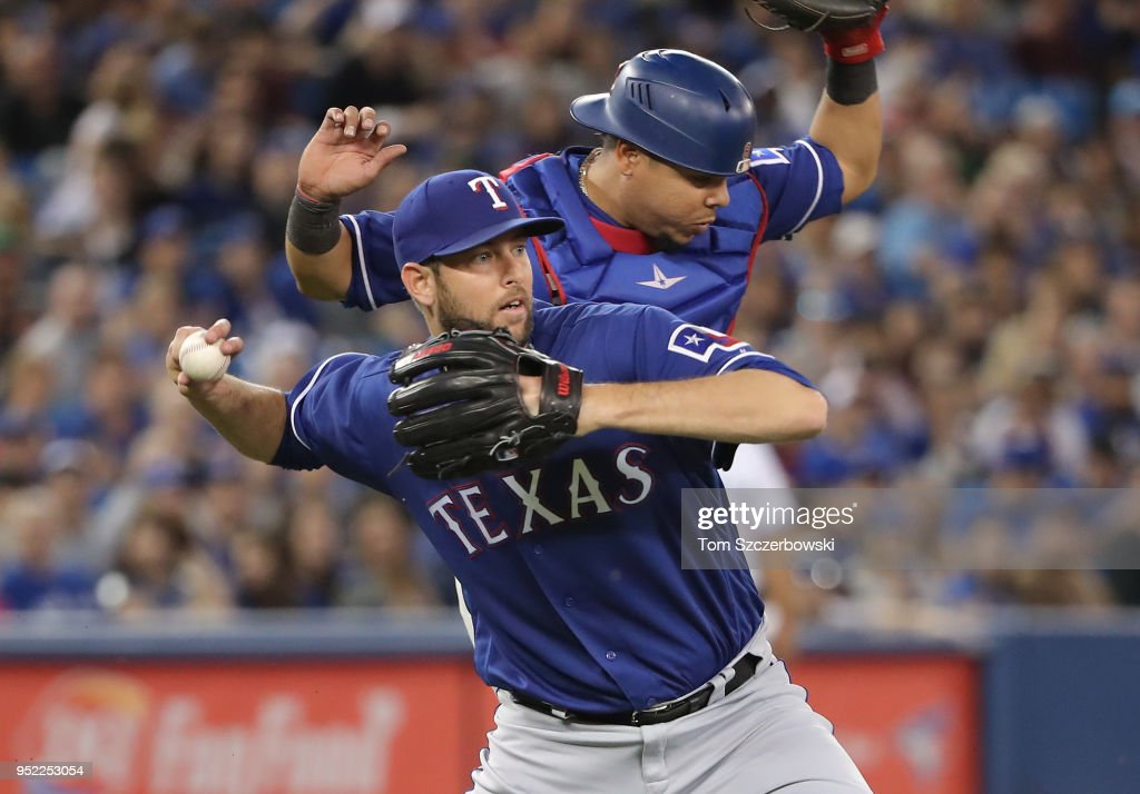 Chris Martin #31 of the Texas Rangers throws out the baserunner as he fields a soft grounder and Juan Centeno #8 gets out of his way in the eighth inning during MLB game action against the Toronto Blue Jays at Rogers Centre on April 27, 2018 in Toronto, Canada.