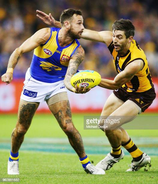 Chris Masten of the Eagles handballs from Ricky Henderson of the Hawks during the round 10 AFL match between the Hawthorn Hawks and the West Coast...