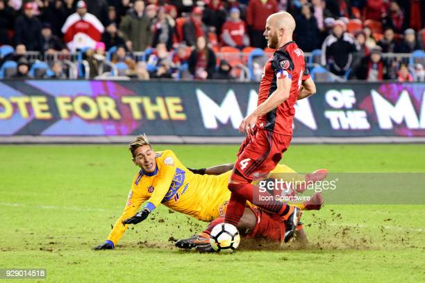 Chris Mavinga of Toronto FC tackles from behind Ismael Sosa of Tigres UANL during extra time of the second half of the CONCACAF Champions League...
