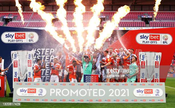 Chris Maxwell of Blackpool lifts the Sky Bet League One Play-off Trophy as his team mates celebrate following victory in the Sky Bet League One...