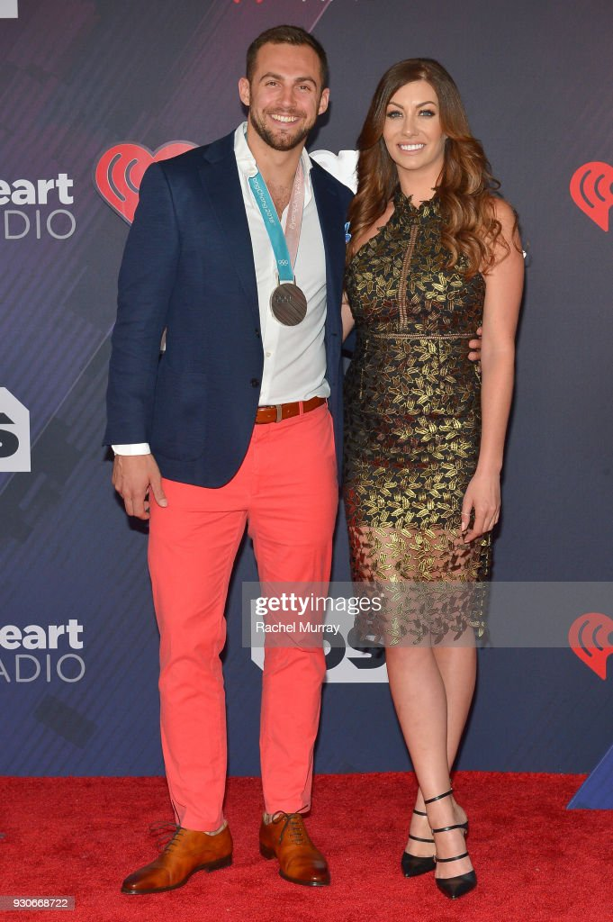 Chris Mazdzer (L) and Mara Marian arrive at the 2018 iHeartRadio Music Awards which broadcasted live on TBS, TNT, and truTV at The Forum on March 11, 2018 in Inglewood, California.
