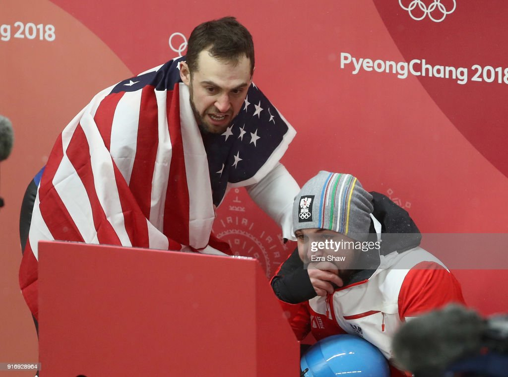 Chris Mazdzer (silver) of the United States and David Gleirscher (gold) of Austria react as they watch the final run of Felix Loch of Germany in the Luge Men's Singles on day two of the PyeongChang 2018 Winter Olympic Games at Olympic Sliding Centre on February 11, 2018 in Pyeongchang-gun, South Korea.