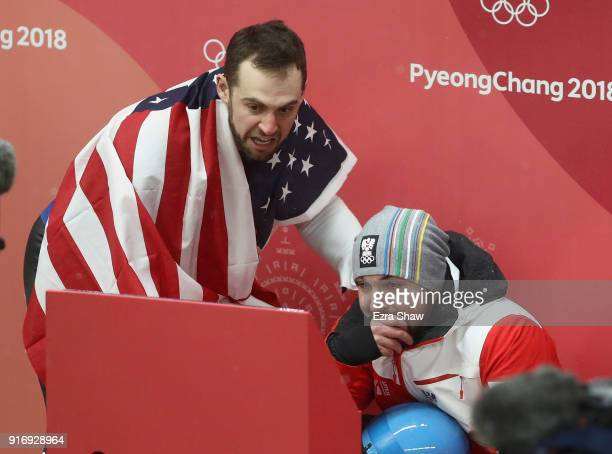 Chris Mazdzer of the United States and David Gleirscher of Austria react as they watch the final run of Felix Loch of Germany in the Luge Men's...