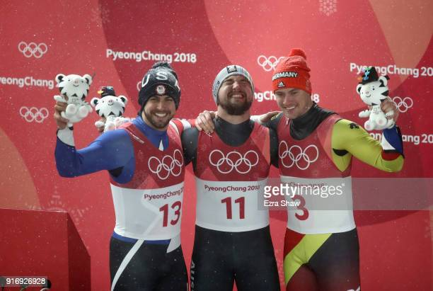 Chris Mazdzer of the United States David Gleirscher of Austria and Johannes Ludwig of Germany celebrate at the flower ceremony following the Luge...