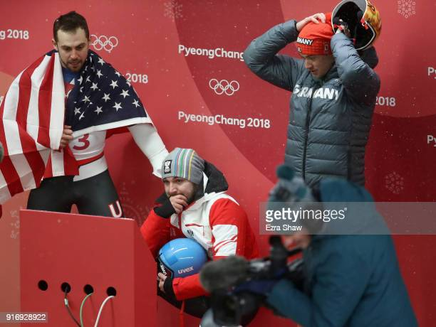 Chris Mazdzer of the United States David Gleirscher of Austria and Johannes Ludwig of Germany react as they watch the final run of Felix Loch of...