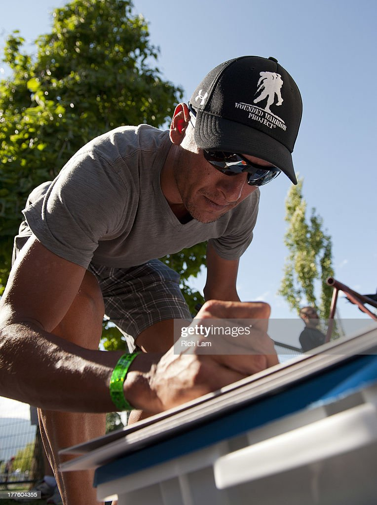 Chris McCormack of New Zealand signs an autograph during the Challenge Penticton Triathlon previews on August 24, 2013 in Penticton, British Columbia, Canada.