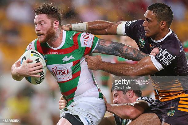 Chris McQueen of the Rabbitohs is tackled by Justin Hodges of the Broncos during the round one NRL match between the Brisbane Broncos and the South...