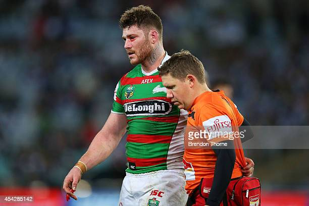 Chris McQueen of the Rabbitohs is taken from the field after a head clash with team mate Luke Keary during the round 25 NRL match between the...