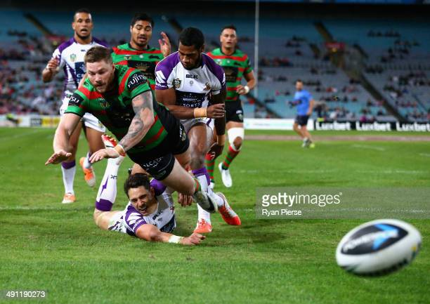 Chris McQueen of the Rabbitohs kicks the ball to deny the try attempt from Billy Slater of the Storm during the round 10 NRL match between the South...