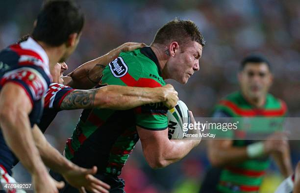 Chris McQueen of the Rabbitohs makes a break from the tackle of Mitchell Pearce during the round one NRL match between the South Sydney Rabbitohs and...