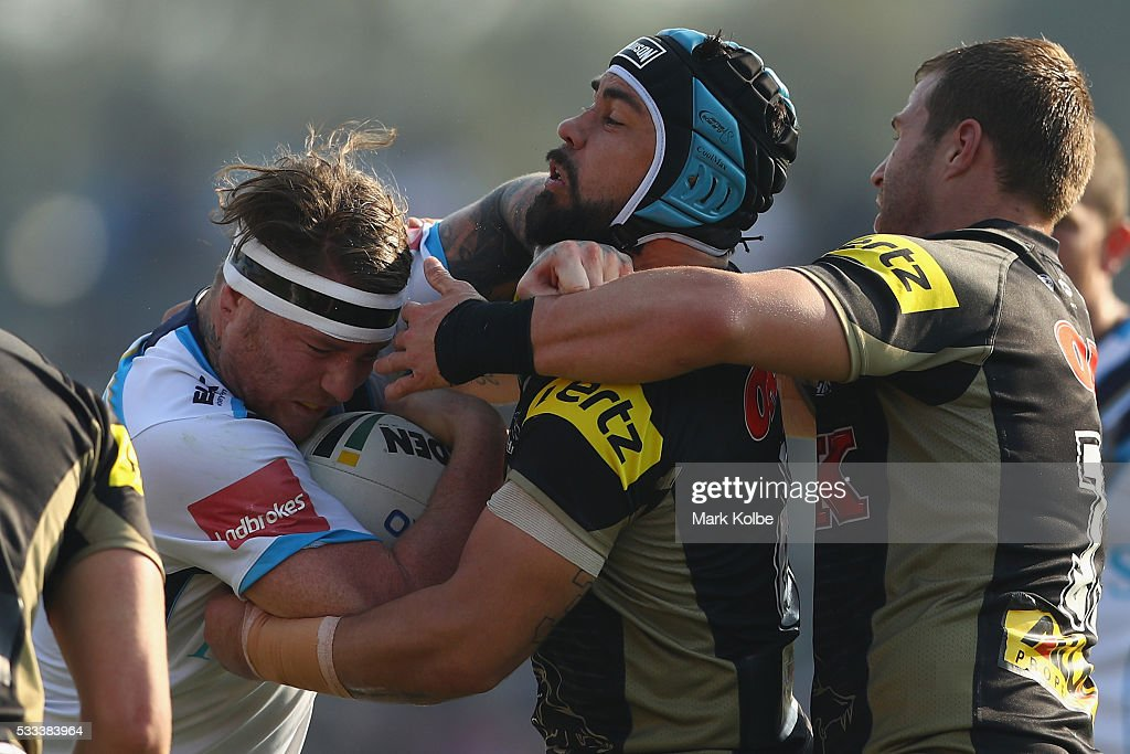 Chris McQueen of the Titans is tackled by Jamie Soward and Trent Merrin of the Panthers during the round 11 NRL match between the Penrith Panthers and the Gold Coast Titans at Pepper Stadium on May 22, 2016 in Sydney, Australia.