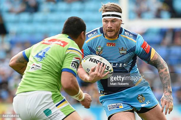 Chris McQueen of the Titans takes on the defence during the round 16 NRL match between the Gold Coast Titans and the Canberra Raiders at Cbus Super...