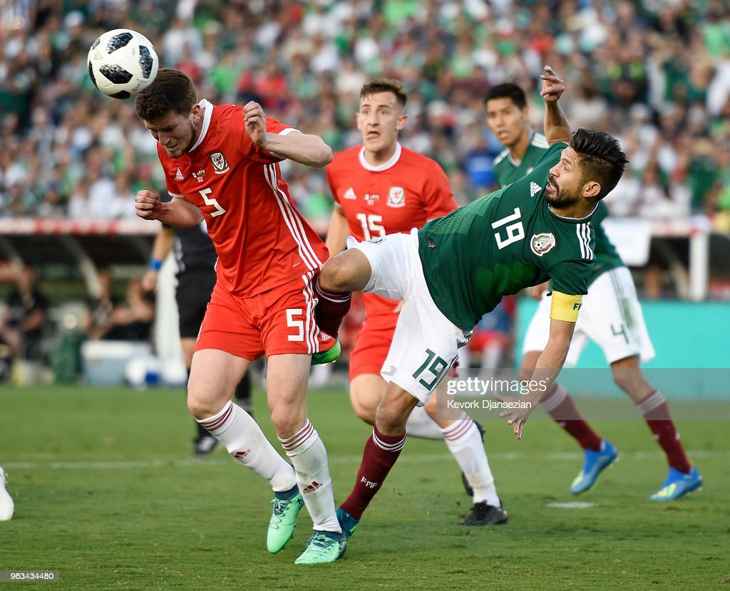 Chris Mepham #5 of Wales clears the ball against Oribe Peralta #19 after a corner kick by Mexico during the second half of their friendly international soccer match at the Rose Bowl on May 28, 2018 in Pasadena, California.
