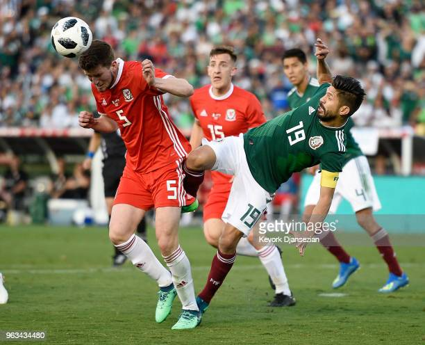 Chris Mepham of Wales clears the ball against Oribe Peralta after a corner kick by Mexico during the second half of their friendly international...
