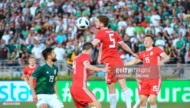 Chris Mepham of Wales heads the ball clear as Oribe Peralta of Mexico watches during their international football friendly at the Rose Bowl in...