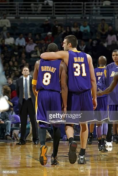 Chris Mihm of the Los Angeles Lakers talks with teammate Kobe Bryant as they walk back to the huddle during a timeout against the Milwaukee Bucks on...
