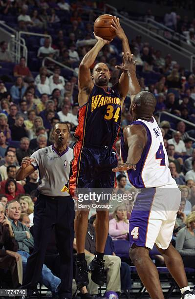 Chris Mills of the Golden State Warriors shoots a jump shot over Alton Ford of the Phoenix Suns during the NBA game at America West Arena on February...