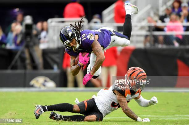 Chris Moore of the Baltimore Ravens is tackled by Jessie Bates of the Cincinnati Bengals during the second half at MT Bank Stadium on October 13 2019...