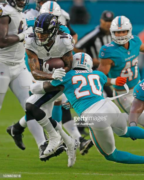 Chris Moore of the Baltimore Ravens is tackled by Reshad Jones of the Miami Dolphins as he runs with the ball during a preseason NFL game on August...